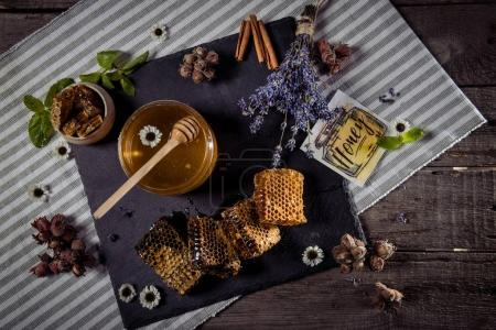 Photo for Top view of fresh honey in glass jar, honeycombs with flowers and card with inscription honey on wooden table - Royalty Free Image