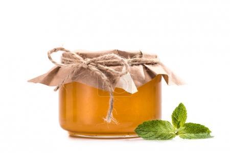Photo pour Vue rapprochée du miel doux frais en verre pot et menthe feuilles isolé sur blanc - image libre de droit