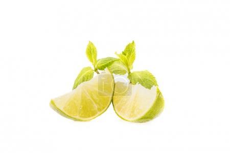 Photo pour Tranches de lime fraîche et feuilles de menthe, isolées sur blanc - image libre de droit