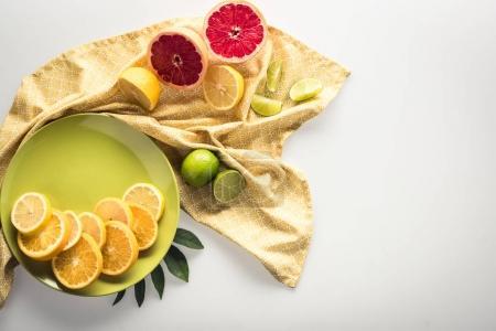 Photo pour Agrumes sur assiette avec nappe, isolés sur blanc - image libre de droit