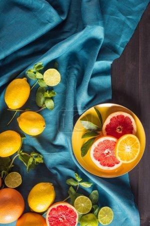 Photo pour Agrumes frais sur assiette avec nappe sur plateau en bois - image libre de droit
