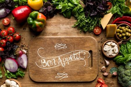Photo for Top view of cutting board, fresh vegetables and herbs on wooden tabletop - Royalty Free Image