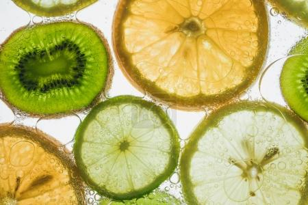 Photo for Fresh kiwi, lime, lemon and orange slices floating in water on white - Royalty Free Image