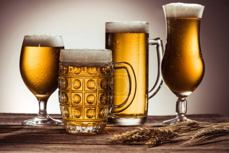 Photo pour Assortiment de bière dans des verres sur table en bois avec épis de blé - image libre de droit