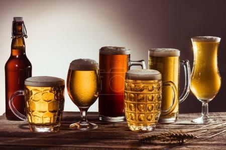 Photo pour Assortiment de bière dans des verres et bouteille sur table en bois avec épis de blé - image libre de droit