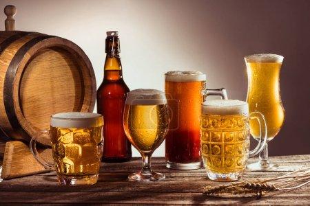 Photo pour Tonneau et bière différente dans des verres et une bouteille sur une table en bois avec des épis de blé - image libre de droit