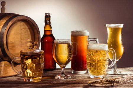 Photo for Barrel and different beer in glasses and bottle on wooden tabletop with wheat ears - Royalty Free Image
