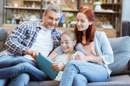 Photo for Smiling parents and teenage girl using digital tablet together at home - Royalty Free Image