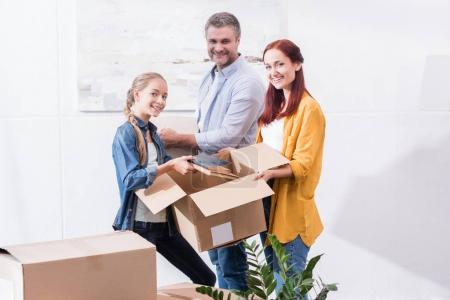 Photo for Parents and teenage girl unpacking boxes while moving together to new home - Royalty Free Image