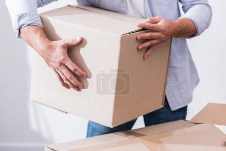 Photo for Partial view of man holding cardboard box in hands - Royalty Free Image
