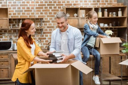 Photo for Happy family unpacking cardboard boxes with stuff together at new home - Royalty Free Image