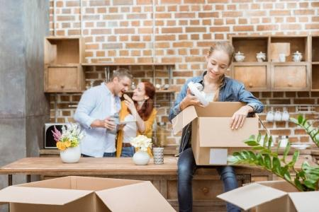 Photo for Smiling teenage girl unpacking cardboard boxes while parents standing behind at new home - Royalty Free Image