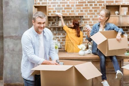 Photo for Selective focus of man looking at camera while unpacking cardboard boxes with family at new home - Royalty Free Image