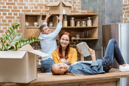 Photo for Smiling teenage girl with book looking at camera while father unpacking cardboard boxes at new home - Royalty Free Image