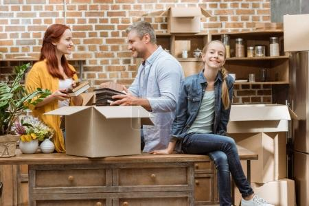 Photo for Happy family unpacking cardboard boxes at new home - Royalty Free Image