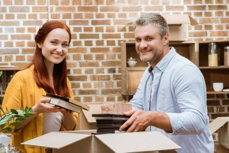 Photo for Portrait of happy couple looking at camera while unpacking box at new home - Royalty Free Image