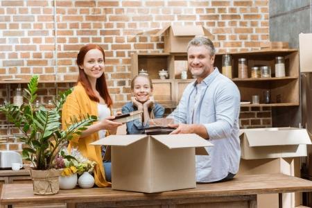 Foto de Familia feliz desembalar cajas de cartón en nuevo hogar - Imagen libre de derechos