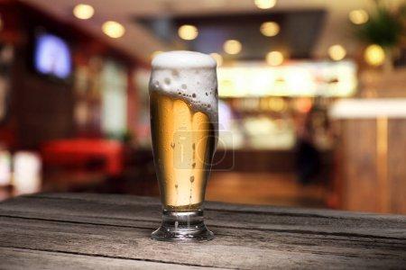 Photo pour Foyer sélectif de tasse de bière debout sur une table en bois dans le bar - image libre de droit
