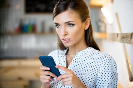Photo for Portrait of beautiful young woman using smartphone and looking away - Royalty Free Image