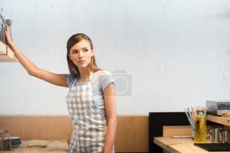 Photo for Beautiful young waitress in apron looking away while working in cafe - Royalty Free Image