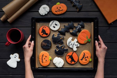 woman holding tray of halloween cookies