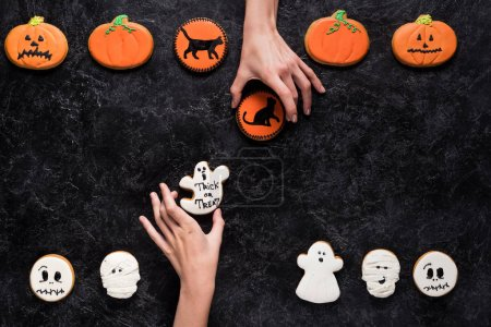 women holding homemade halloween cookies
