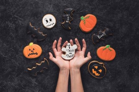 woman holding halloween cookie