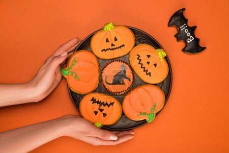 woman holding plate of halloween cookies