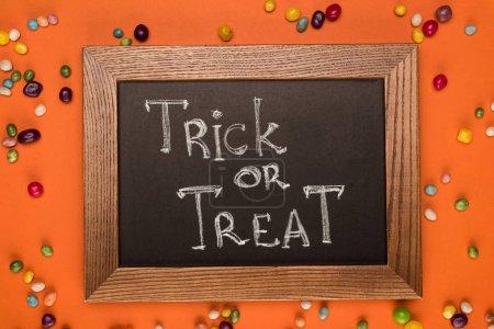 Foto de Vista superior de pizarra con truco o tratar la inscripción en la mesa naranja con dulces - Imagen libre de derechos