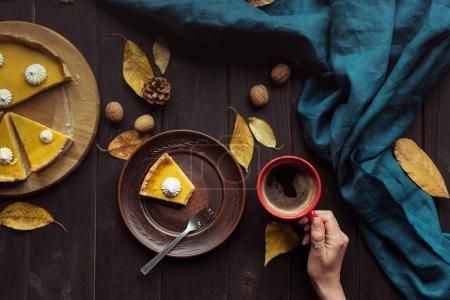Photo for Top view shot of pumpkin pie on wooden table and female hand holding a cup of coffee over it. - Royalty Free Image