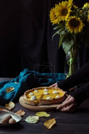 Female hands placing pie on table