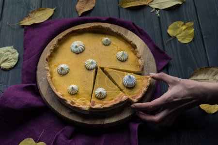 Photo for Closeup shot of female hands taking a piece of pumpkin pie, placed on wooden table covered with autumn leaves - Royalty Free Image