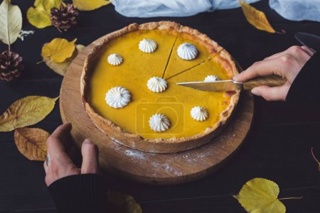 Female hands cutting pumpkin pie