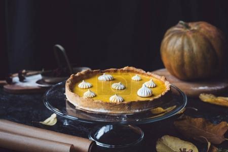 Photo pour Composition avec tarte à la citrouille sur support de gâteau en verre, feuilles d'automne et citrouille en arrière-plan - image libre de droit