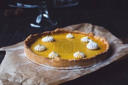 Photo pour Gros plan d'une tarte à la citrouille fraîche avec de la meringue placée sur du papier parchemin brun - image libre de droit
