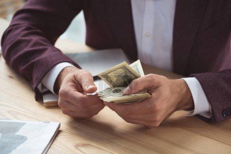 businessman counting dollar banknotes