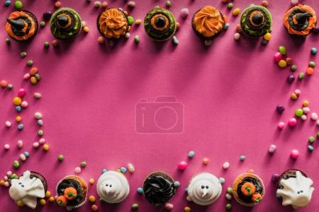 Photo for Top view of various decorative halloween cupcakes and colorful candies on pink - Royalty Free Image