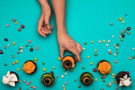 hands and halloween cupcakes