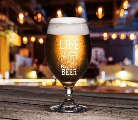 Photo pour Mise au point sélective du verre de standing de bière sur la table dans la pub - image libre de droit