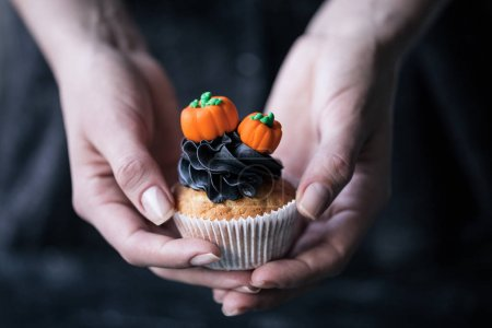 Photo for Close-up partial view of person holding halloween cupcake with pumpkins - Royalty Free Image