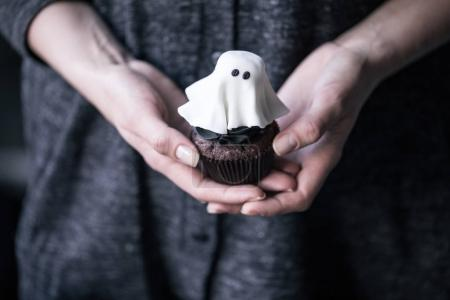 Photo for Close-up partial view of human hands holding halloween ghost cupcake - Royalty Free Image