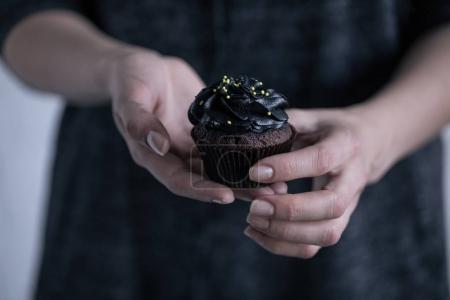 Hands holding halloween cupcake