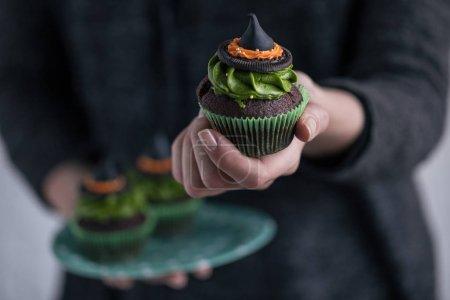 person holding halloween cupcake