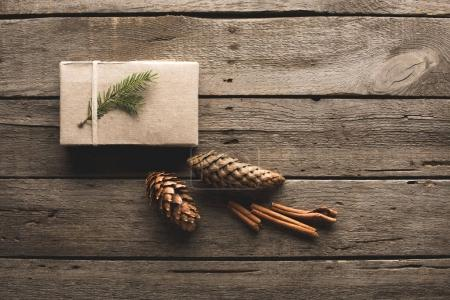gift with pine cones and cinnamon sticks
