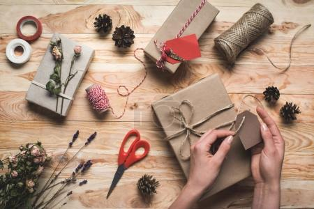woman decorating christmas gift