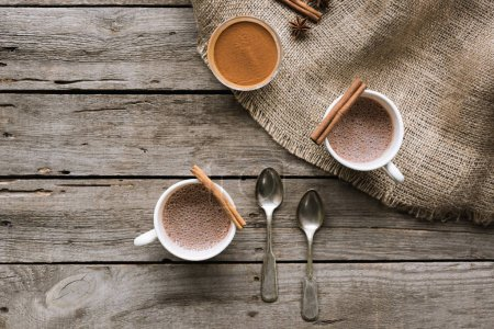 cups of cacao and spices on table