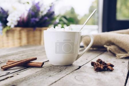 Photo pour Foyer sélectif de tasse de cacao avec guimauve douce et épices sur table en bois - image libre de droit