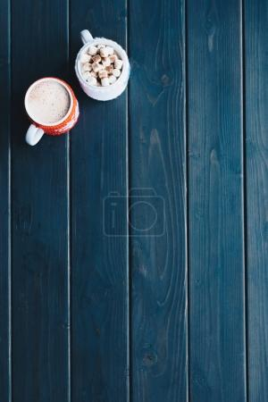 Photo for Top view of cups of freshly made cacao drink on wooden tabletop - Royalty Free Image