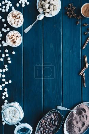 Photo for Flat lay with cups of fresh cacao drink and various spices on wooden surface - Royalty Free Image