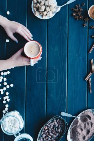 Female hands holding cup of cacao